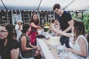 Hochzeitsgast mit Hochzeitstorte bei einer Do It Yourself Hochzeit im Garten