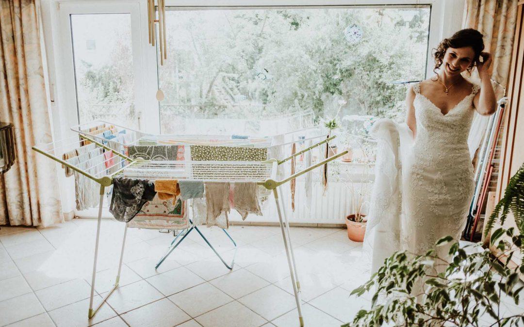 Braut im Hochzeitskleid in ihrem Wohnzimmer