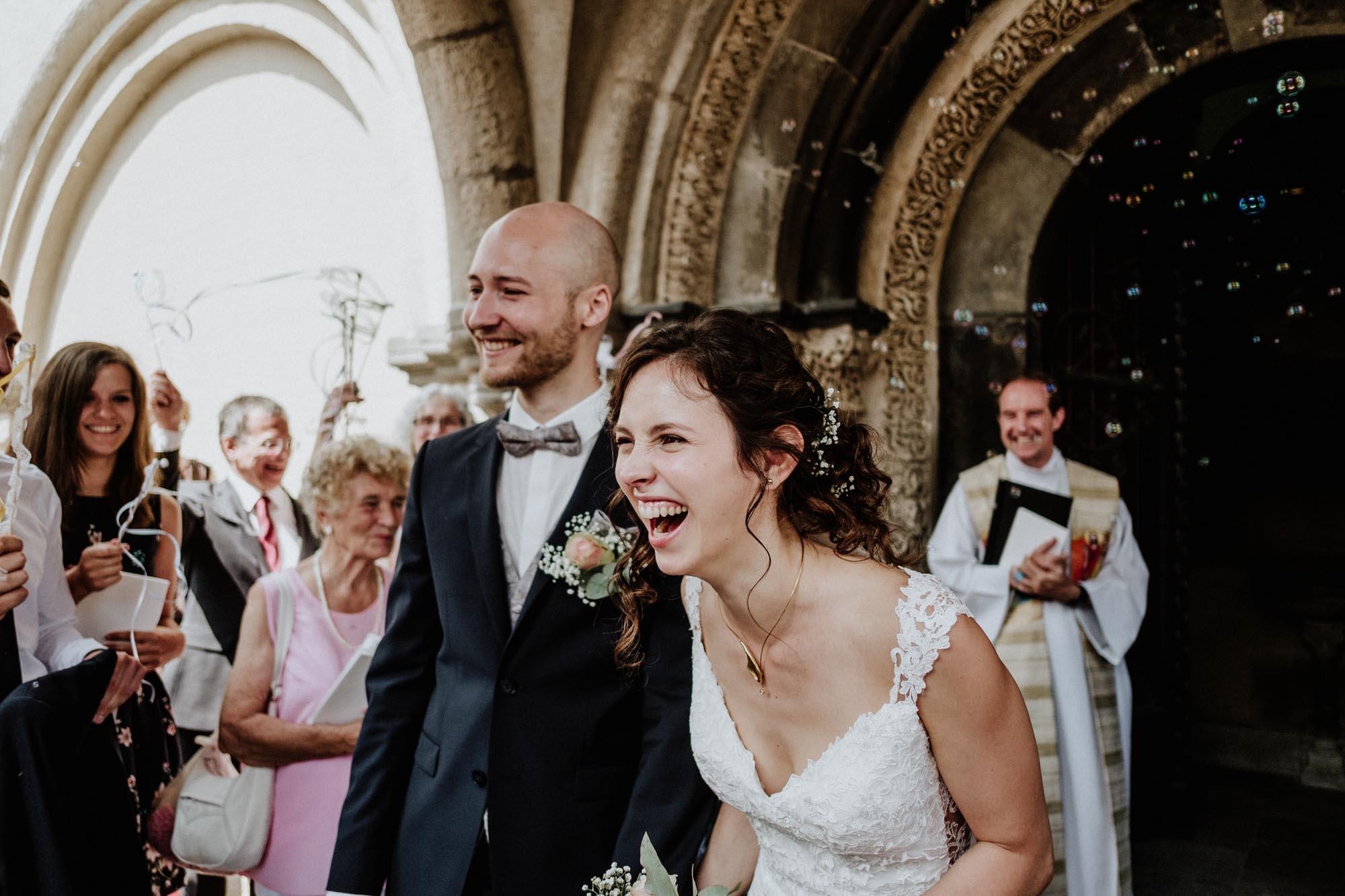 Hochzeitsfoto einer lachenden Braut nach der kirchlichen Trauung an Ihrem Hochzeitstag