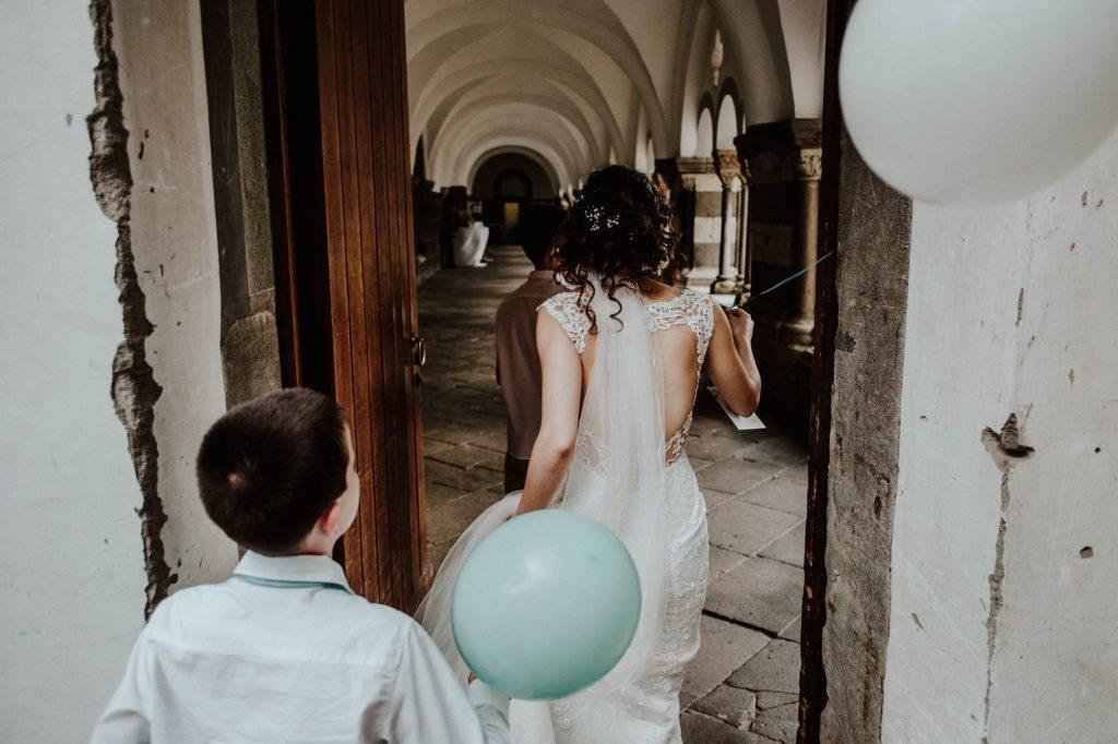 Braut geht im rückenfreien Hochzeitskleid durch eine Tür der Abtei Brauweiler