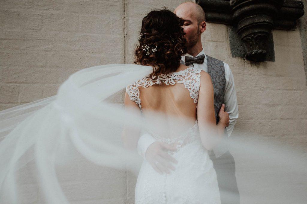 Hochzeitsfoto einer Braut im rückenfreien Brautkleid mit langem Schleier