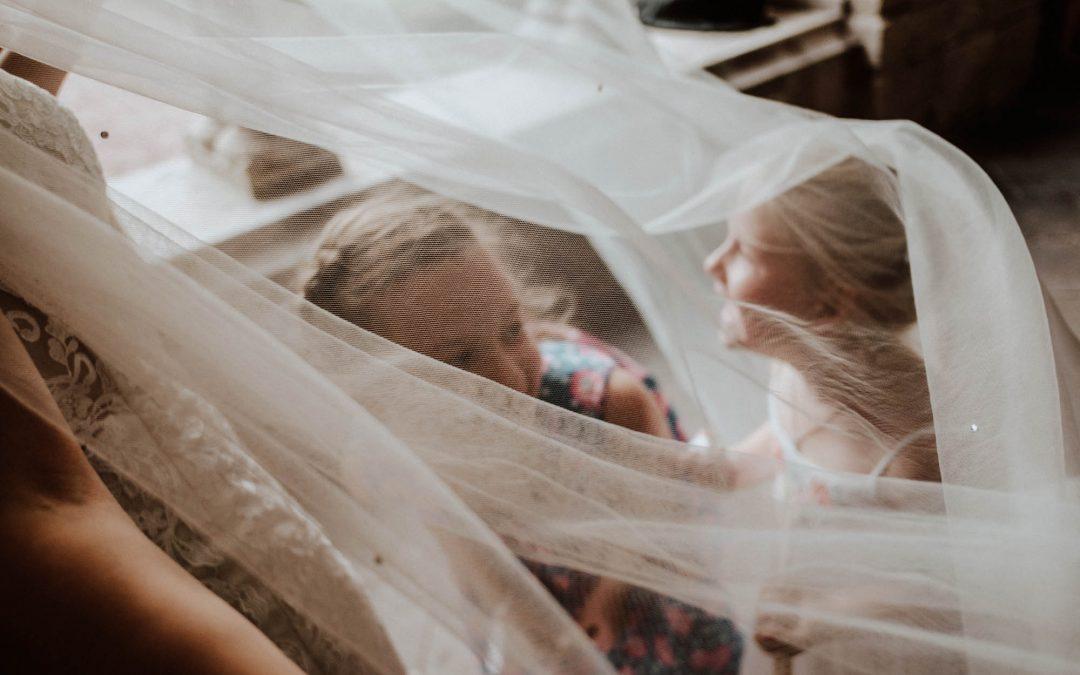 Kinder verstecken sich unter Brautschleier bei Hochzeitsfest in der Abtei Brauweiler