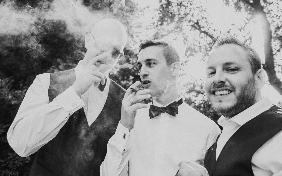 Bräutigam und Trauzeugen rauchen Zigarre