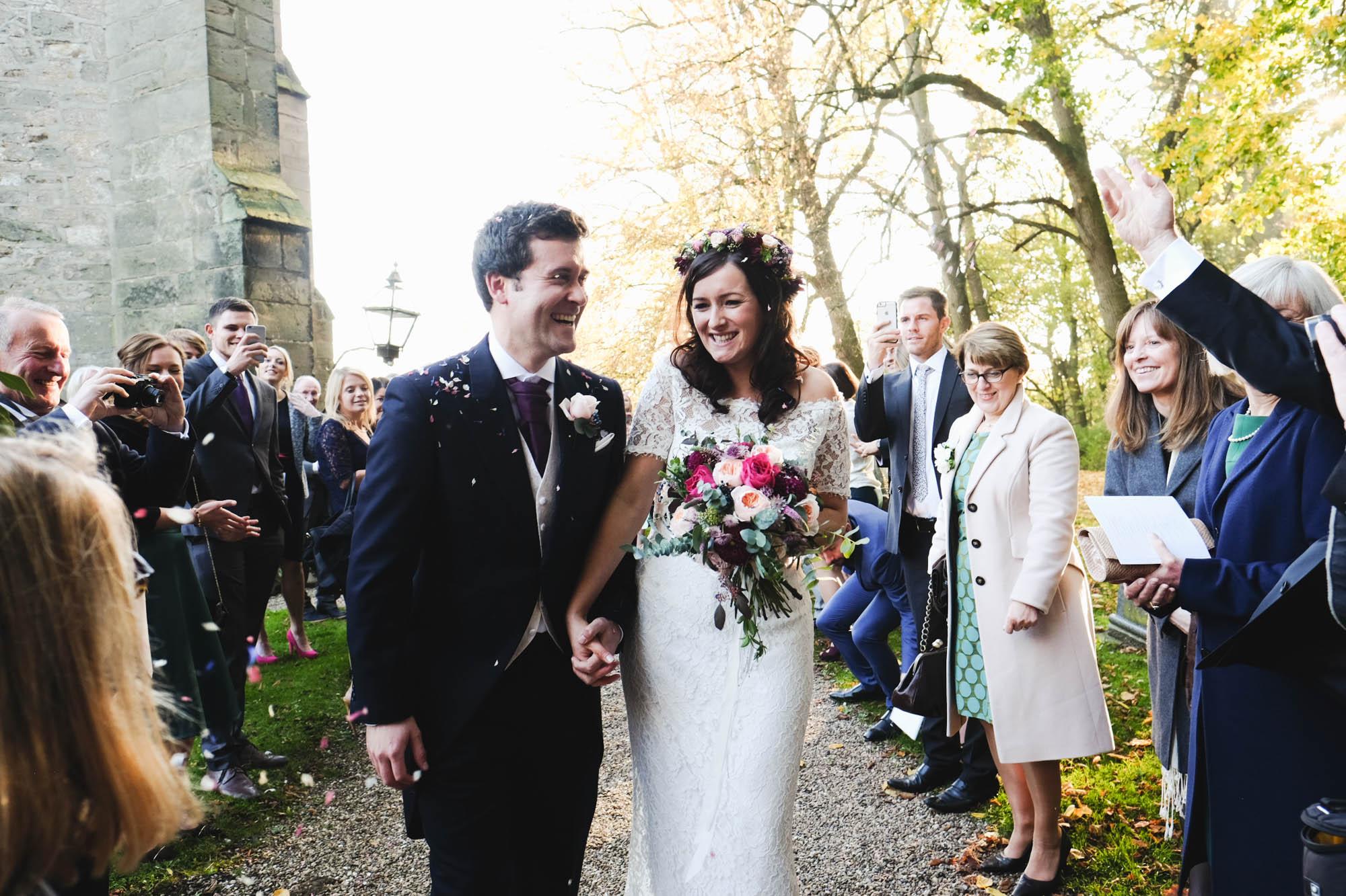 Brautpaar im Konfettiregen nach der Trauung in England