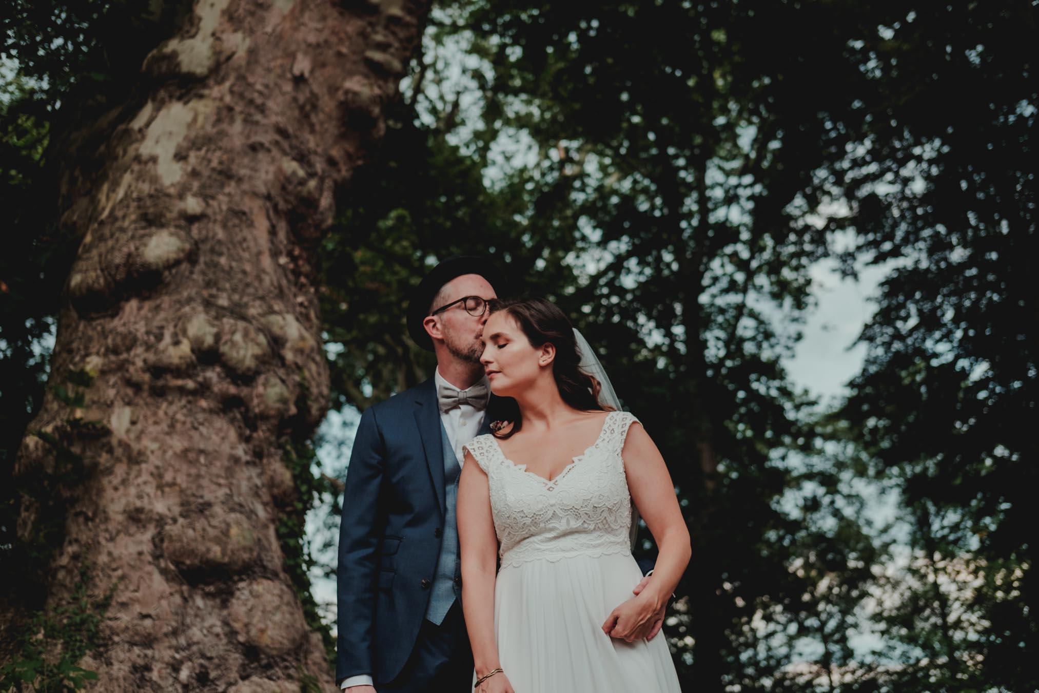 Hochzeitspaar steht unter einem alten Baum im Rittergut Orr bei Köln