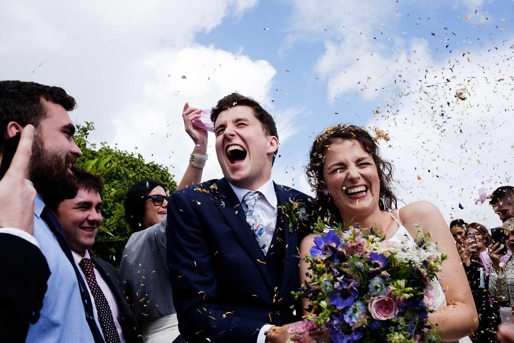 Lachendes Hochzeitspaar im Konfettiregen