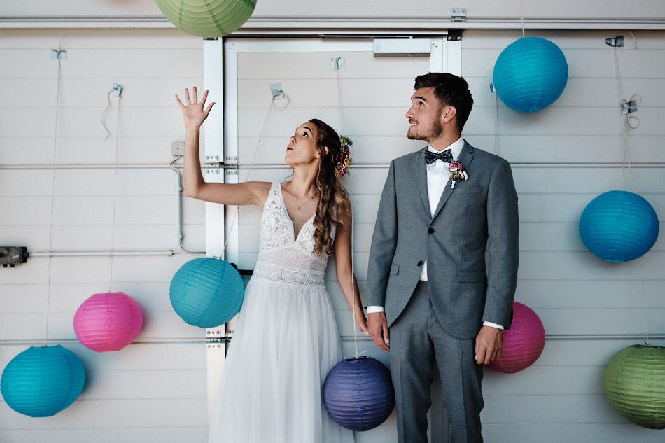 Braut und Bräutigam beim Paarshooting umgeben von bunten Lampignipignons
