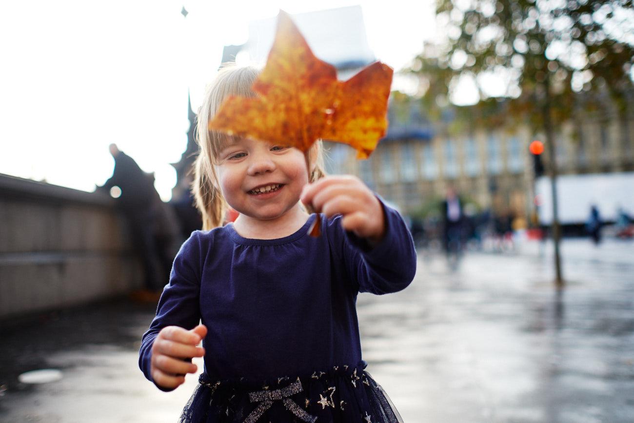 Ein kleines Mädchen hält ein Herbstblatt in die Kamera