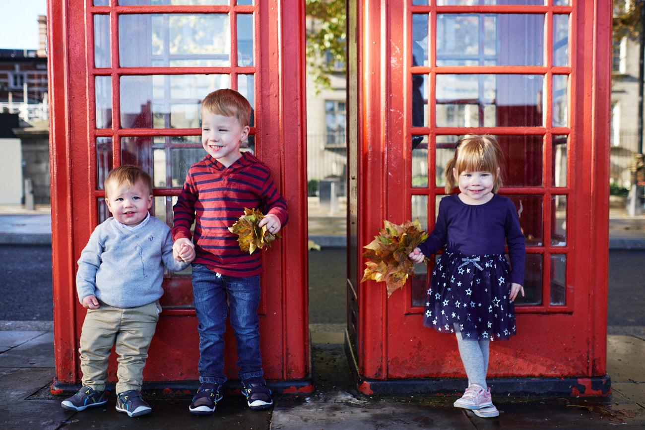 Kinder vor englischen Telefonzellen mit Herbstlaub in den Händen
