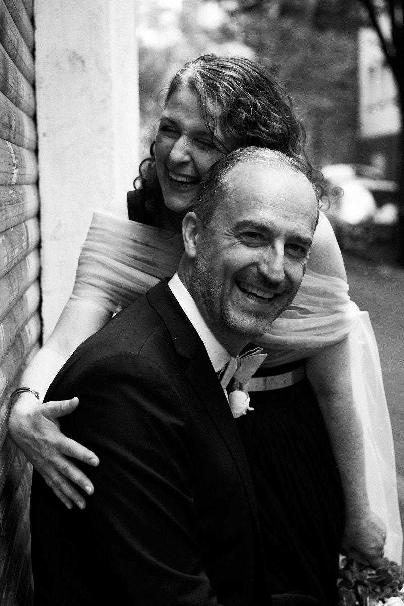 Braut umarmt lachend ihren Bräutigam