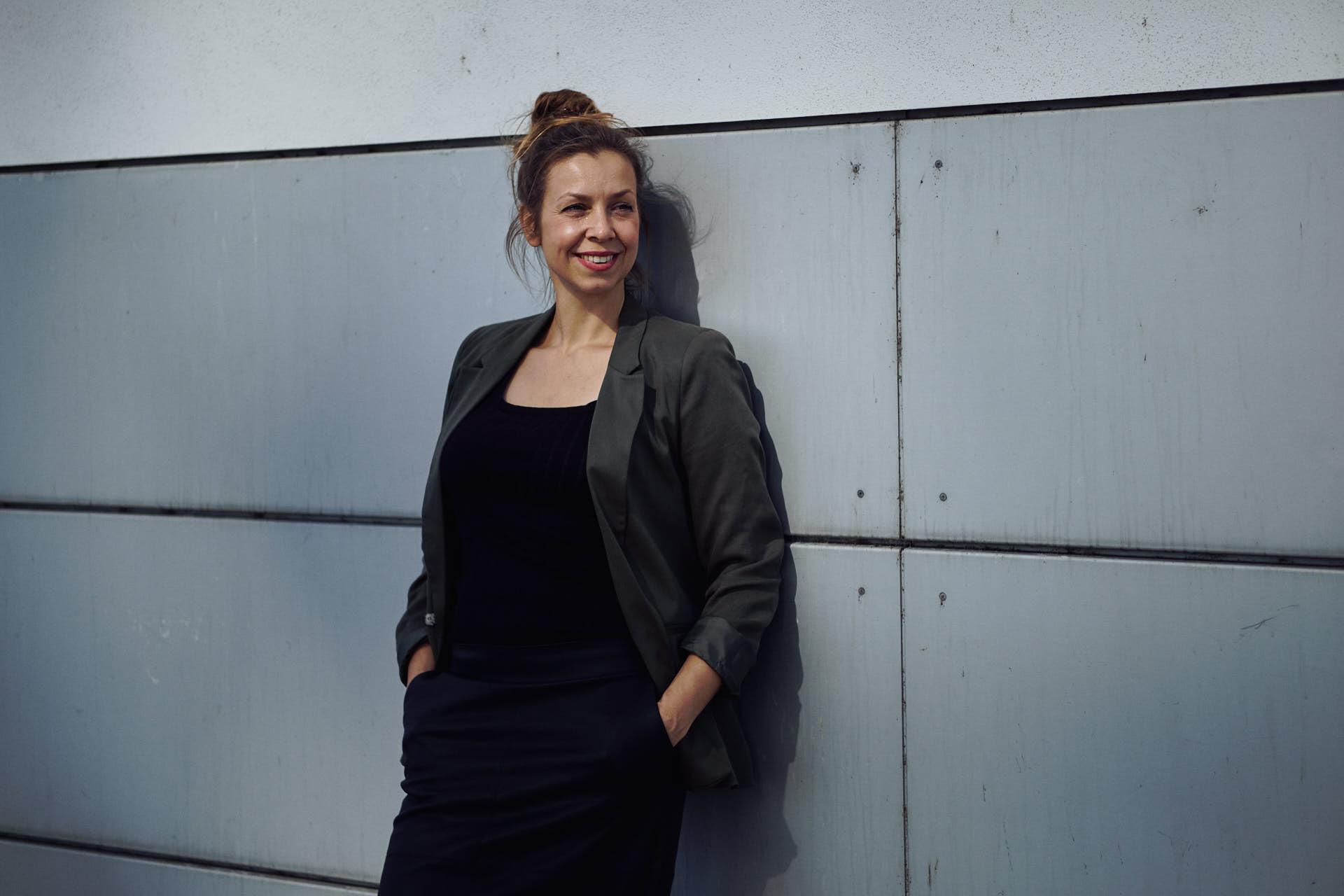 Rauchentwöhnuns Coach Nicole Gabor posiert vor einer Wand für ein Business Portrait in Köln