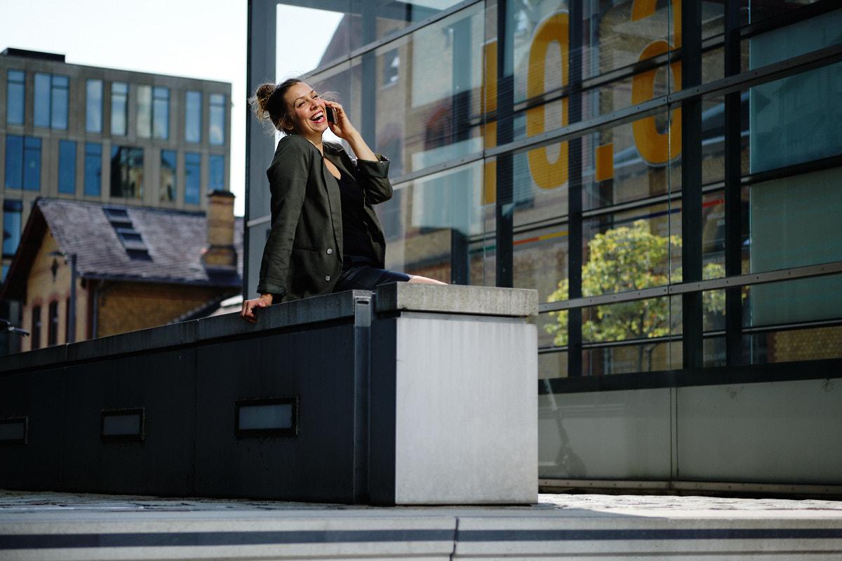 Nicole Gabor posiert mit Handy inmitten kühler Business Fassade