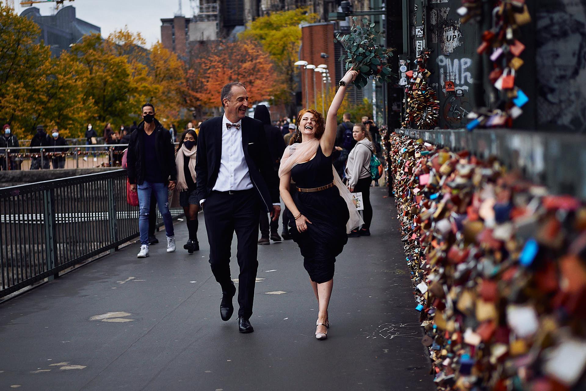Hochzeitspaar Spaziert über die Hohenzollernbrücke in Köln die Braut wirft Ihren Brautstrauss in die Luft