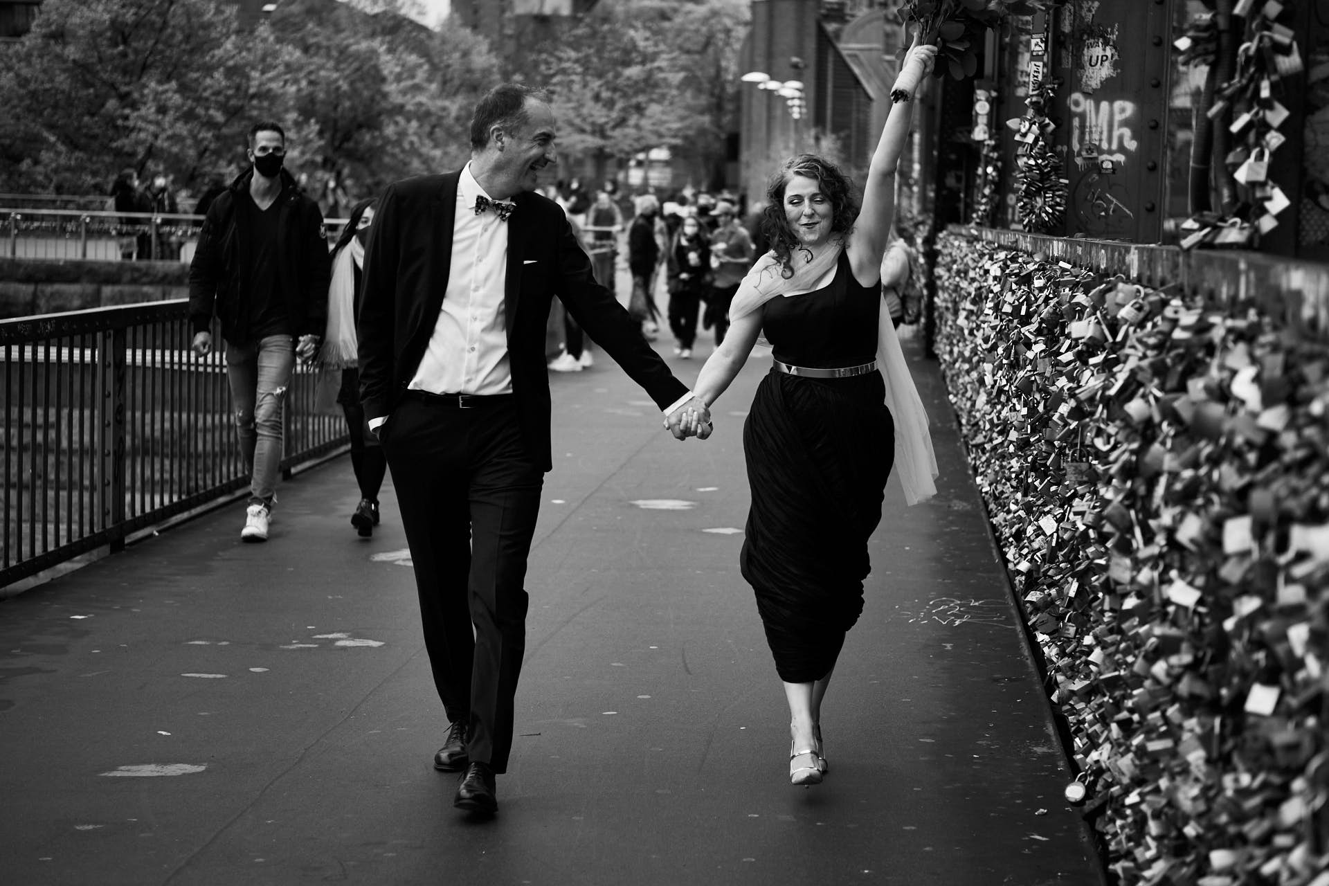 Hochzeitspaar beim Spaziergang über die Hohenzollernbrücke in Köln