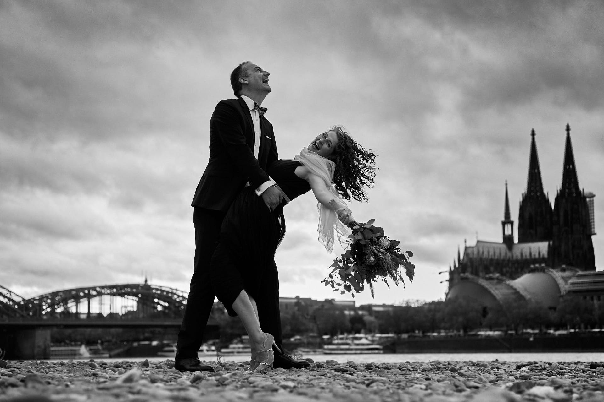 Brautpaar tanzt am Rheinufer mit dem Kölner Dom im Hintergrund