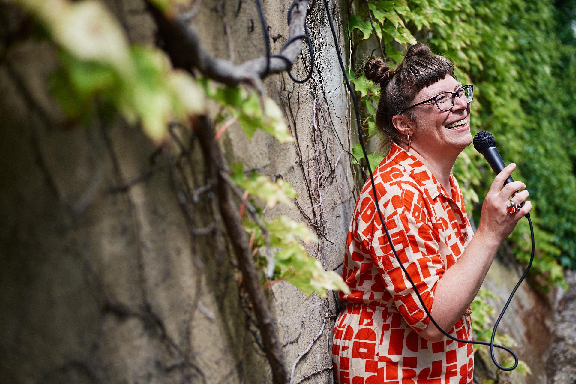 Sängerin Gitte Wolffson lehnt gegen eine Efeu bewachsene Wand und hält ein Mikrofon