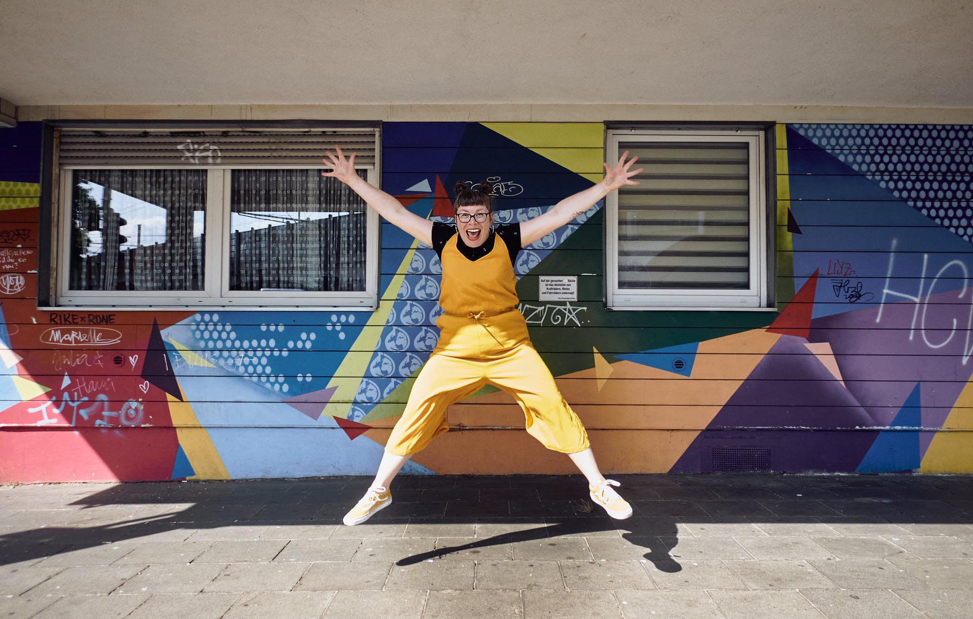 Sängerin Gitte Wolffson springt vor einer bunten Fassade hoch in die Luft