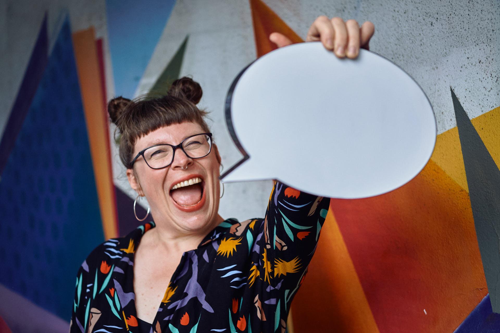 Sängerin Gitte Wolffson hält lachend eine Sprechblase hoch