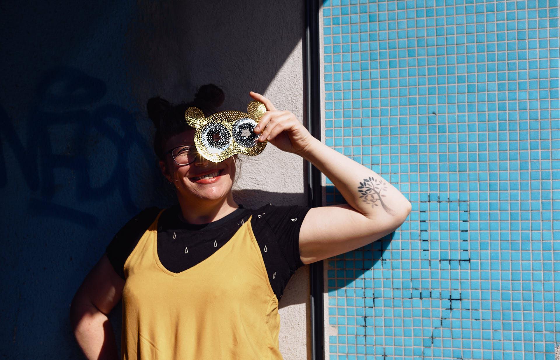 Sängerin Gitte Wolffson vor einer Blau gekachelten Wand eine glitzernde Maske vors Gesicht haltend
