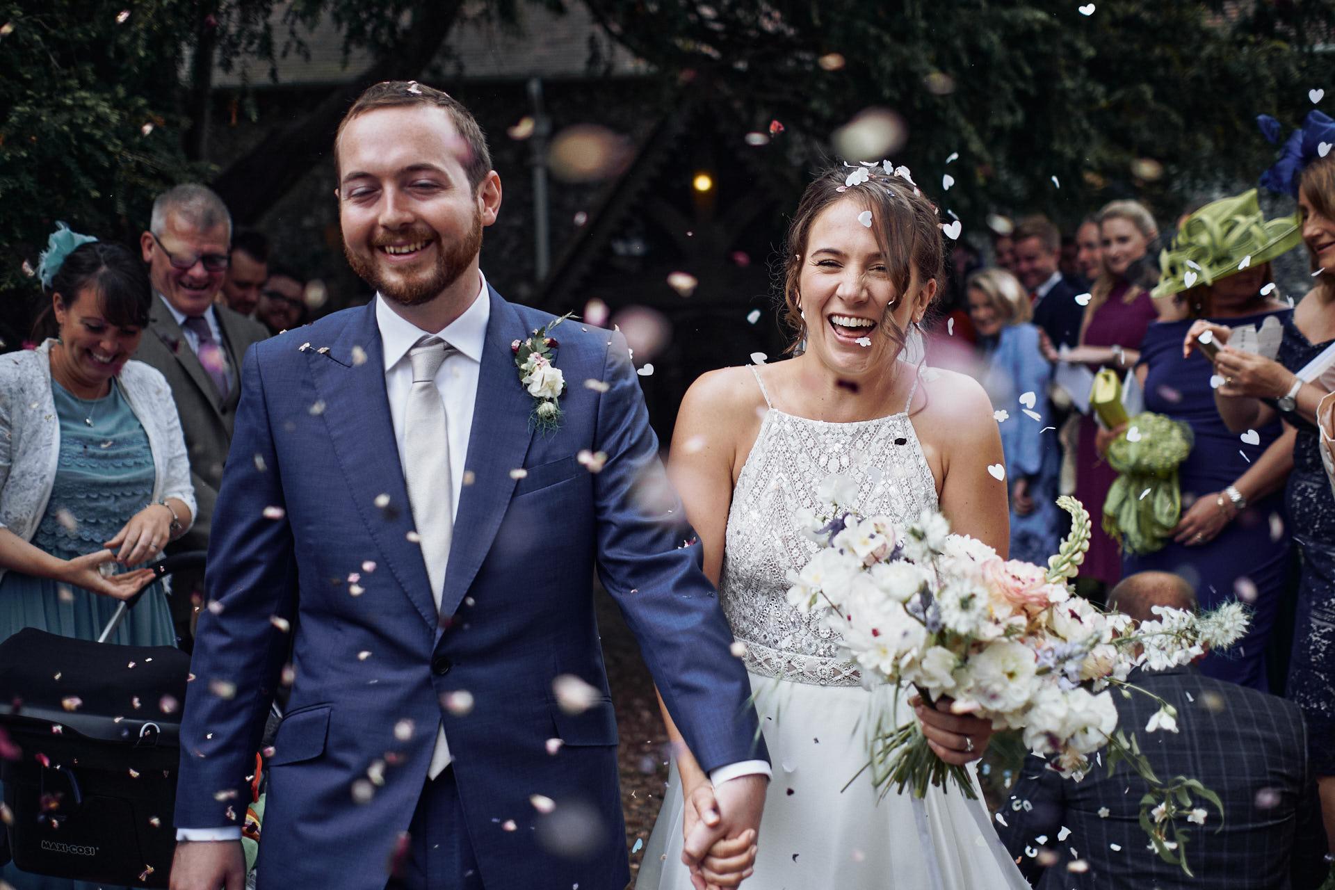 Braut und Bräutigam im Konfettiregen beim Auszug aus der Kirche in Köln
