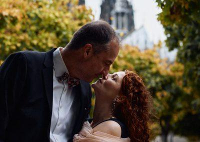Ein sich küssendes in einer Allee, im Hintergrund der Kölner Dom