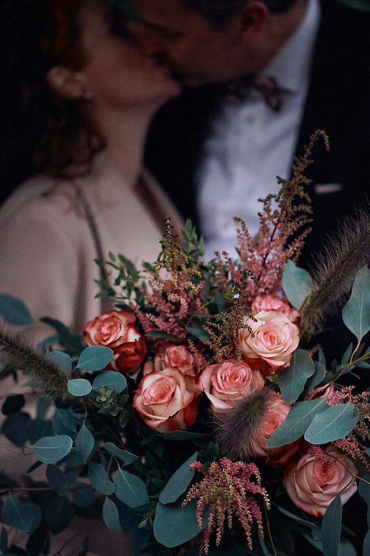 Ein opulenter Brautstrauss mit Rosen im Hintergrund küsst sich das Hochzeitspaar