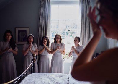 Braut wird vom ihren Brautjungfern beim First Look bewundert