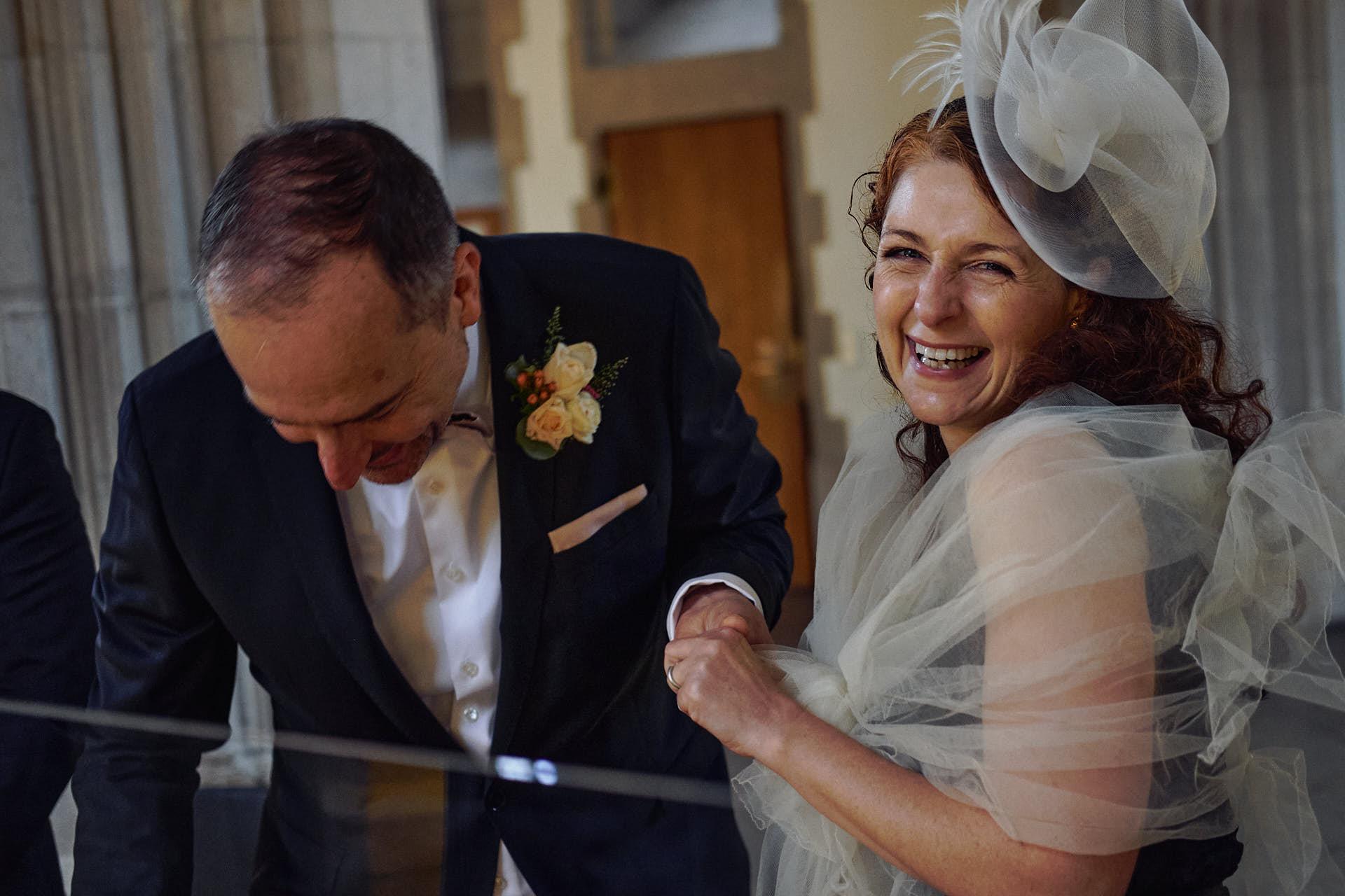Braut lacht beim Ringtausch, da der Ehering dem Bräutigam nicht mehr passt