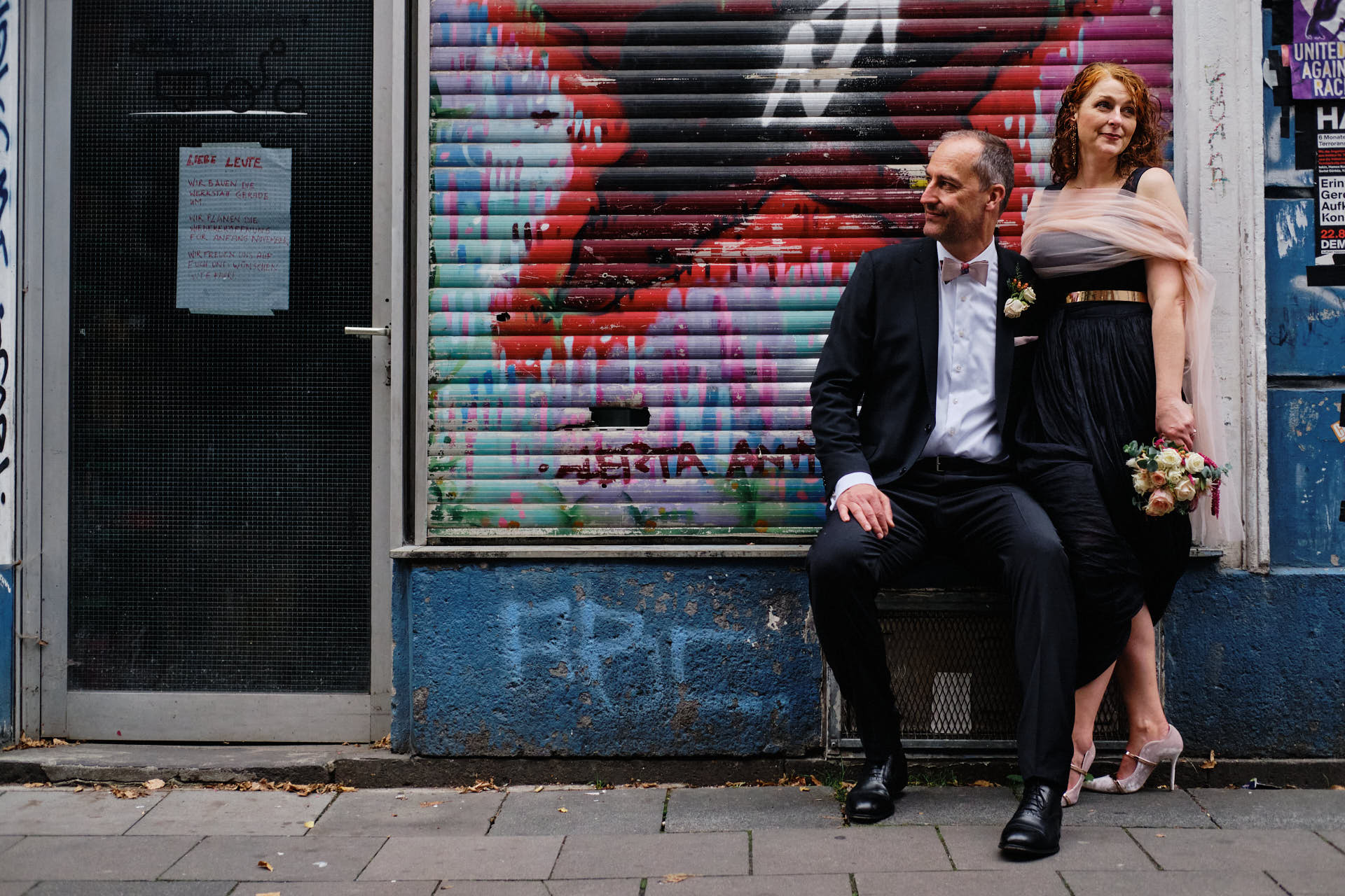 Hochzeitspaar posiert vor einer Grafittiwand in Köln