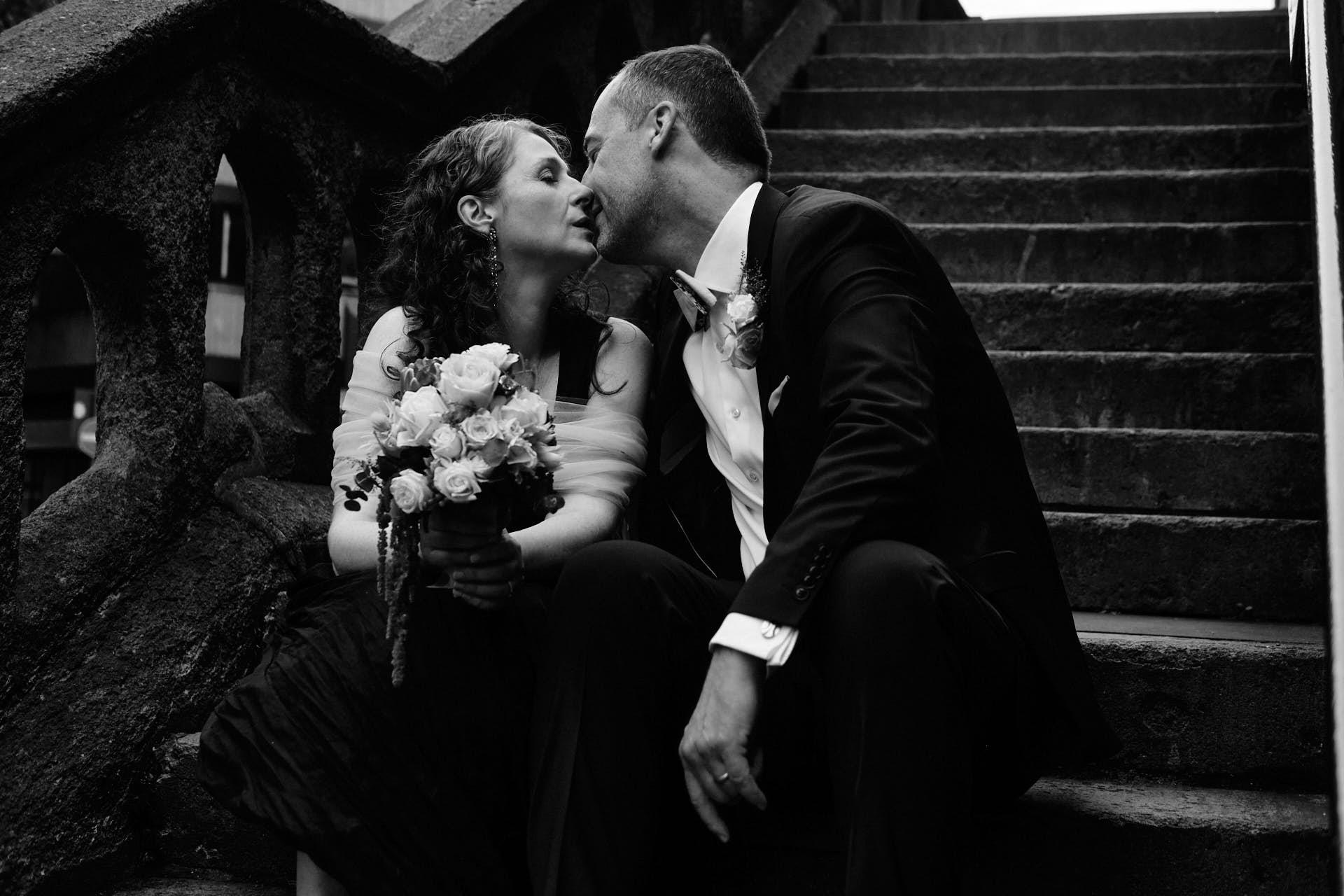 Hochzeitspaar küsst sich auf der Treppe der Severinstorburg in Köln sitzend